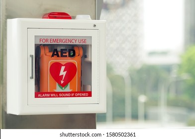 General view of a life saving defibrillator. Portable automated external defibrillator (AED) mounted on the wall in public restroom at airport.