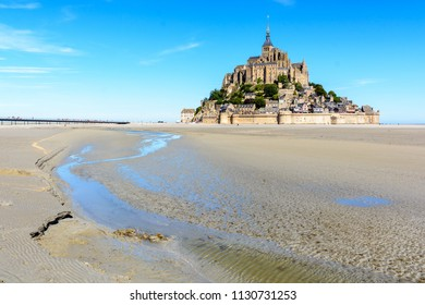 General view of the Mont Saint-Michel tidal island, located in France in Normandy, from the bay at low tide under a summer blue sky with a small stream winding in the sand in the foreground.
