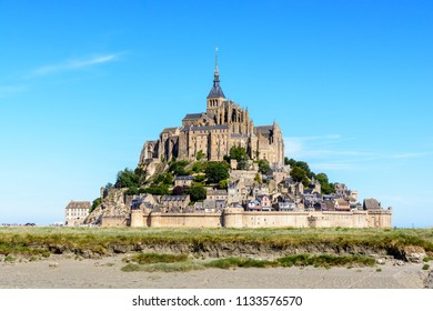 General view of the Mont Saint-Michel tidal island, located in France on the limit between Normandy and Brittany, from the bay at low tide under a summer blue sky with saltmarsh in the foreground.