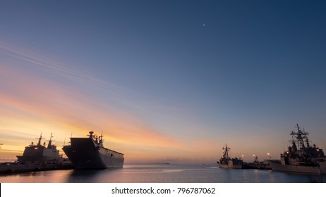 a general view of a spanish naval base. Frigates and a carrier ship moored in a harbour at sunrise.