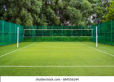 General view of the sports playground in the park with artificial grass and a stretched net on a background of green trees