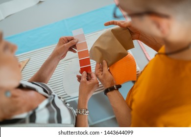Generating ideas. Two modern fashion designers holding color samples while choosing a color palette for a new collection