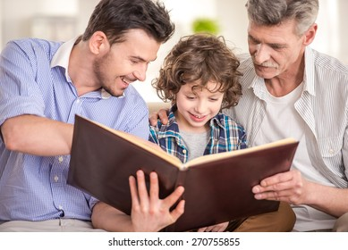 Generation portrait. Grandfather, father and son sitting and reading a book on sofa.