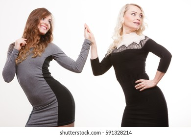 Generation relationship and outfit concept. Portrait adult daughter with mother. Two attractive elegant women wearing dresses, long curly hairs blonde mom and brown haired girl