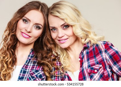 Generation and relationship. Portrait adult daughter with mother. Two gorgeous casual style women long hair blonde mom and brown haired girl, studio shot