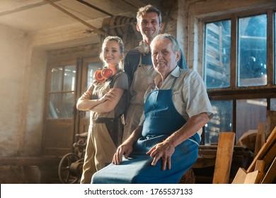 Generationen von Zimmerleuten in ihrer Familienwerkstatt mit Blick auf die Kamera