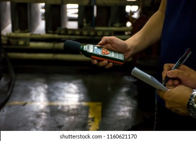 Generator factory, Singapore - 10 July 2018. Engineer use sound level meter to measure sound level of generator and recording data.