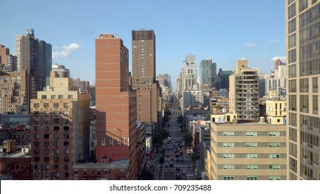 Generic aerial overhead view of urban city landscape down straight avenue road between tall buildings