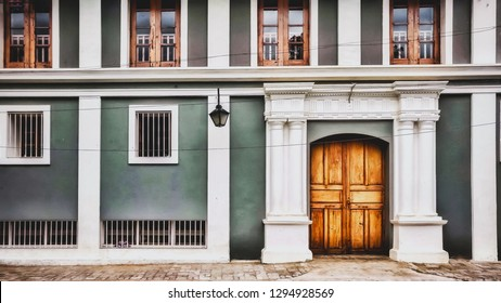 A generic building in pondicherry made in Ashram style, with gray color walls and a beautiful wooden door in pondicherry in the Ashram area of Pondicherry, white town, India.