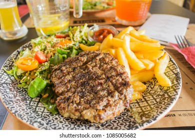 Generic burger with salad and fries on a table served in a restaurant.