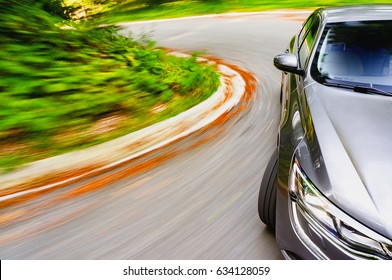 Generic car driving fast on a curved road