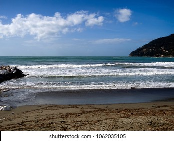 Generic coastline with breaking waves and horizon, sandy beach. Sunny day. Europe, Italy. Blue sky, sea.