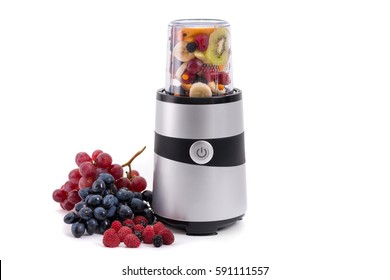 Generic fruit blender and juicer with recipient filled with sliced fruits and fresh grapes and raspberries on the side isolated on white