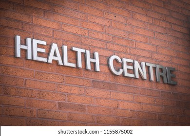 A generic health centre sign on a brick building