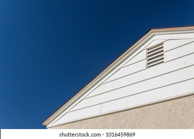 Generic house view of side and roof edge, stucco and vinyl with attic ventilation set against a deep blue sky, copy space, horizontal aspect