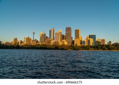 generic modern cityscape with water reflection in warm sunset, harbour city with skyscraper skyline in business district