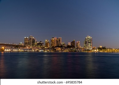generic modern cityscape with water reflection in night, harbor city with downtown skyscraper in business district Sydney