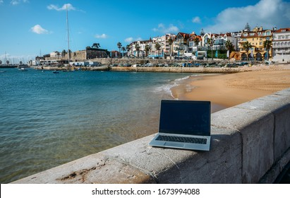 Generic notebook laptop on sunny deserted sandy beach backround. Paradise home-office concept especially during Coronavirus Covid-19 outbreak