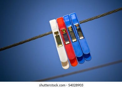 Generic pegs on a washing line in clear blue sky