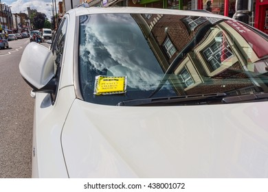 Generic penalty charge notice (parking fine) attached to windscreen of white car parked on street in London England