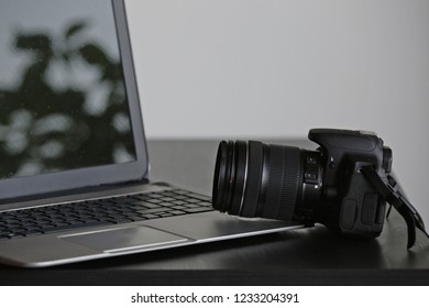 A generic professional digital reflex camera with its big lens leaning on a laptop. A concept about photography bussiness. In the reflective screen, some spots are visible. Plenty of negative space.