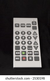 A generic remote control with large buttons is isolated on black, some room for copy on top, vertical