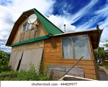 generic rural summer dacha residential house with satellite antenna situated nearby city outskirts in central russia against scenic sky detail wide panoramic view