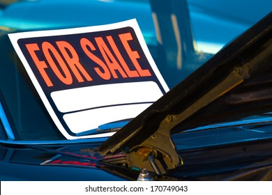 Generic for sale sign mounted on the windshield of a used car.