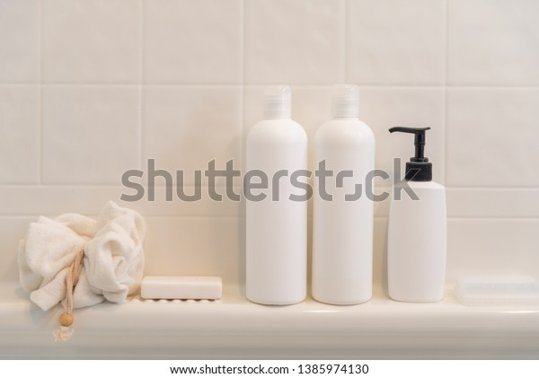 Generic shampoo and conditioner bottles, a soap dispenser, bar of soap, terry cloth scrubber and nail brush on a shelf in a bathroom
