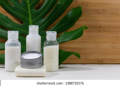 Generic soap, shampoo, conditioner, body wash and tooth cleaning powder on glossy green leaf and a bamboo background. Natural, eco friendly, vegan, zero waste, organic lifestyle concept options