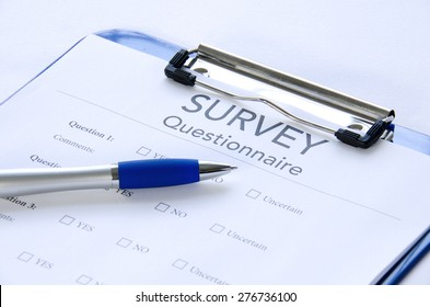 Generic survey questionnaire clipped to a blue clipboard with a pen sitting on it