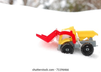 A Generic Toy Snow Plow on a Bed of White Snow with Trees in the Distant Background, Room for Text