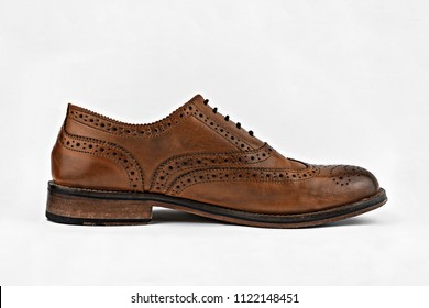 Generic unbranded classic brown brogue shoe from the side in a white studio.