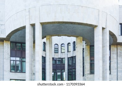 Generic urban city modern style white building exterior with semicircular ledge with columns. Old town big house with white wall and pillars