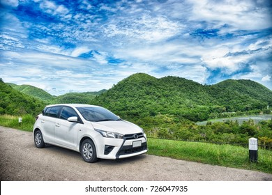 Generic White Car with beautiful nice blue sky & mountains as background
