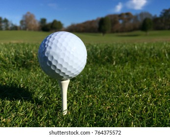 Generic white golf ball sit on tee over green grass on a golf course waiting to be hit by player club down fairway. Low angle view on beautiful autumn day