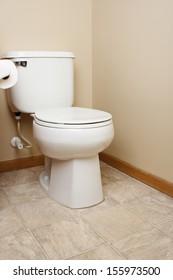 Generic white toilet in tan walled bathroom