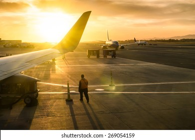 Generic working man walking near airplane wing at terminal gate of international airport at sunset - Concept of emotional travel around the world - Soft focus and sun lens flare due to backlighting