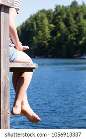 a generic young woman reads a book on the dock overlooking the lake at the cottage