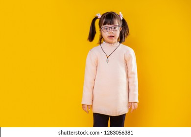 Genetic disorder child. Curious little girl with down syndrome posing against orange wall wearing soft warm sweater
