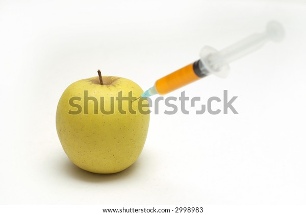 Genetic modification food concept of apple on spoon with medical injection and needle with orange fluid