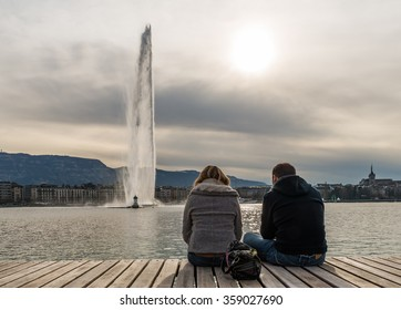 Geneva City Switzerland Silhouette Romantic Couple sit on Wooden Jetty at Bains des Paquis with Out of Focus Jet d'Eau large fountain skyline cityscape under Dramatic Golden Cloudy Sky in Autumn