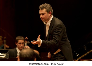 GENEVA - MARCH 16: Conductor Antoine Marguier conducts the United Nations Orchestra at the Victoria Hall March 16, 2012 in Geneva, Switzerland.