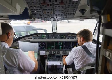 GENEVA - SEPTEMBER 11: Etihad Regional pilots in aircraft cockpit on September 11, 2014 in Geneva, Switzerland. Darwin Airline, operating under the brand name Etihad Regional since January 2014