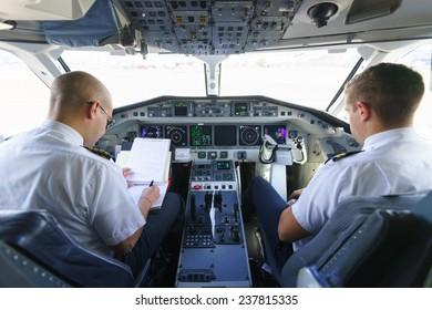GENEVA - SEPTEMBER 16: Etihad Regional pilots in aircraft cockpit on September 16, 2014 in Geneva, Switzerland. Darwin Airline, operating under the brand name Etihad Regional since January 2014