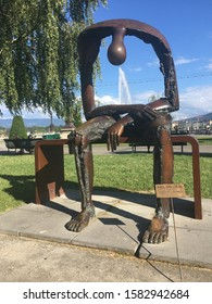 Geneva, Switzerland - 09/04/2018: Melancholy, a sculpture by Albert Gyorgy, depicts the emptiness experienced during the grief process. The Jet d'Eau makes the sculpture appear to be crying.