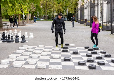 Geneva, Switzerland - April 16, 2019: People playing traditional oversized street checkers game in Parc des Bastions - image