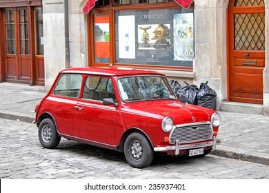 GENEVA, SWITZERLAND - AUGUST 4, 2014: Red classical car Austin Mini Cooper at the city street.