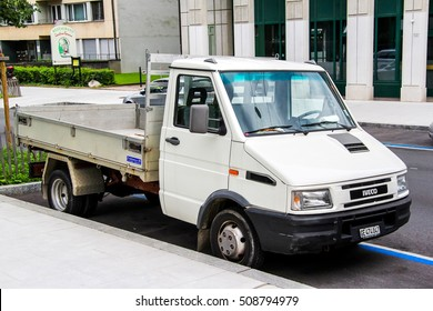 GENEVA, SWITZERLAND - AUGUST 4, 2014: White flat-bed cargo truck Iveco Daily in the city street.