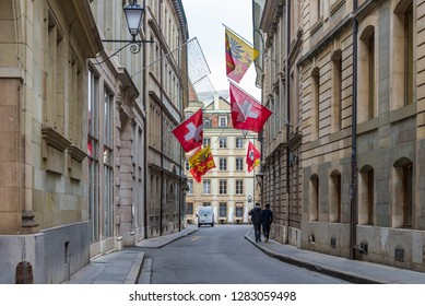 GENEVA, SWITZERLAND - DECEMBER 2018: Outdoor street view on the street along with old buildings and Swiss decorated flags in Geneva, Switzerland.